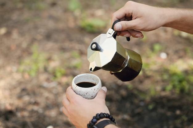 Homme buvant du café en forêt