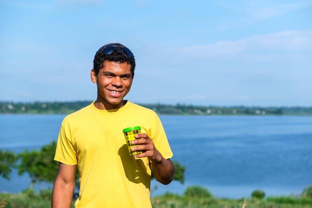 Homme buvant du café en plein air en été près de la rivière