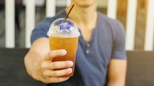 Homme buvant un thé aux fruits glacé dans un café.