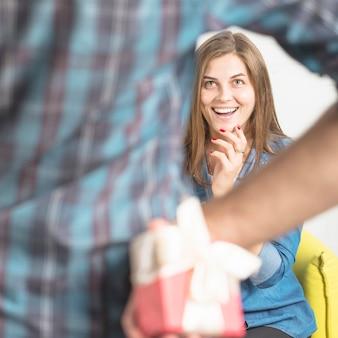 Homme cachant le cadeau surprise de sa copine heureuse