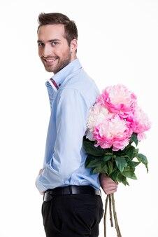 Homme cachant une fleur derrière son dos isolé sur fond blanc.