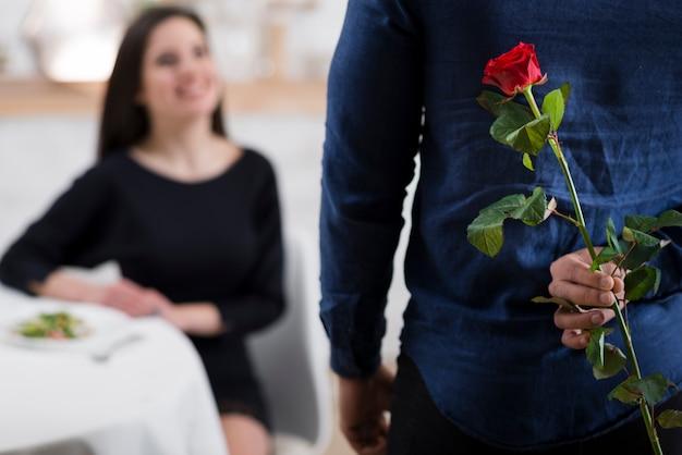 Homme cachant une rose rouge de sa petite amie