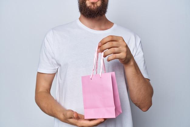 L'homme en cadeau de paquet rose tshirt blanc montre un autre
