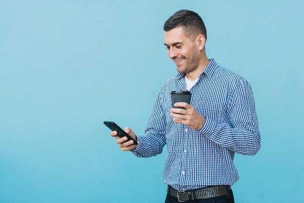 Homme avec café et smartphone en milieu urbain