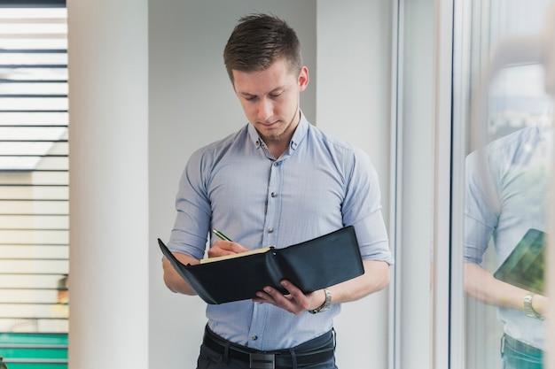 Un homme avec un cahier posant au bureau
