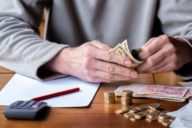 Homme avec calculatrice comptant, prenant des notes à la maison, la main est écrite dans un cahier. pièces empilées disposées à deesk. notion de finances d'épargne.