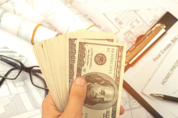 Un homme calcule le coût de construction d'une maison selon des plans. photo de bureau avec projets d'architecte et presse-papiers