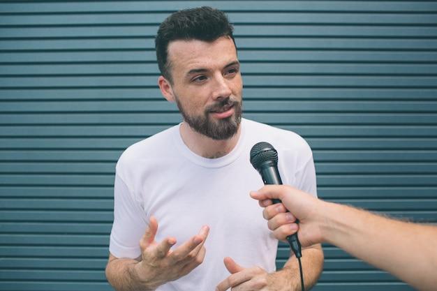 Un homme calme et concentré est debout et parle au micro. il regarde une personne tenant un micro. guy agite les mains. il sourit un peu. isolé sur rayé
