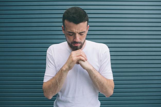 Un homme calme et paisible est debout et tient les poings ensemble. il garde les yeux fermés. la tête de guy est baissée. l'homme se concentre sur le praaying. isolé sur rayé.