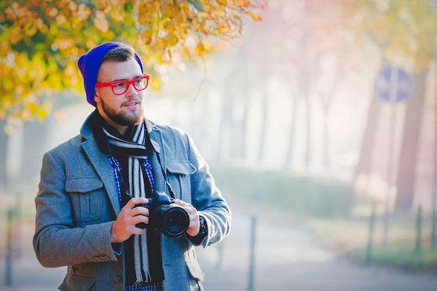 Homme avec caméra dans l'allée de la saison d'automne