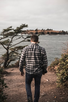 Homme avec caméra marche vers la rivière