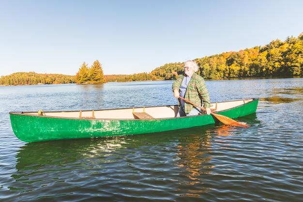 Homme avec canoë au lac un jour d'automne ensoleillé