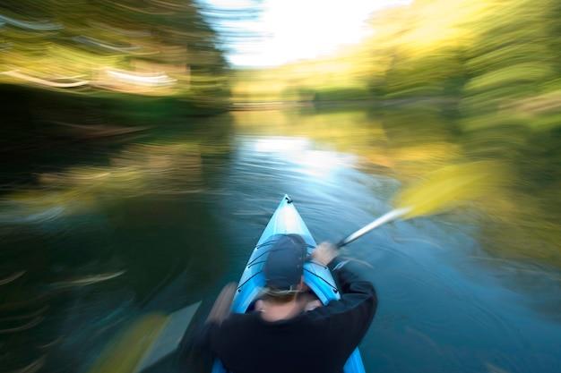 Homme en canoë avec des feuilles floues