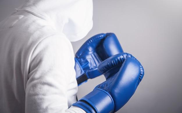 Homme à capuche avec des gants de boxe.