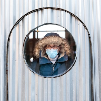 Homme avec un capuchon regarde par la fenêtre ronde, portant un masque facial de protection