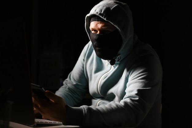 Homme carder dans un masque se connecter à darknet