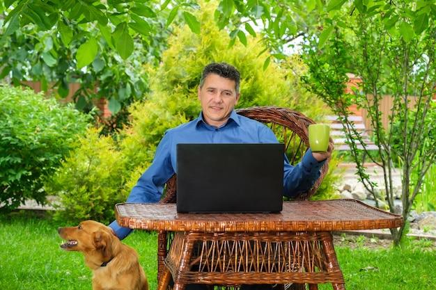 Homme caressant un chien buvant du café analysant des informations web et lisant des nouvelles