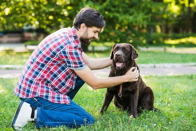Homme caressant son chien dans le parc