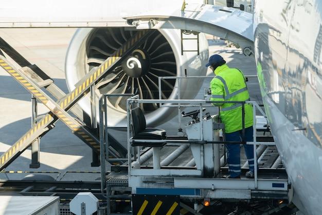 Un homme cargo sur une plate-forme de chargement charge du fret aérien à un avion cargo.