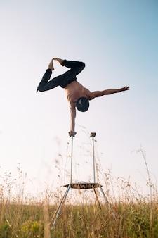 Un homme de carrure athlétique effectue des exercices de gymnastique complexes dans un champ au coucher du soleil