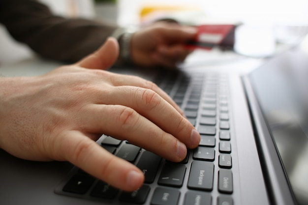 Homme avec carte bancaire en tapant sur ordinateur portable