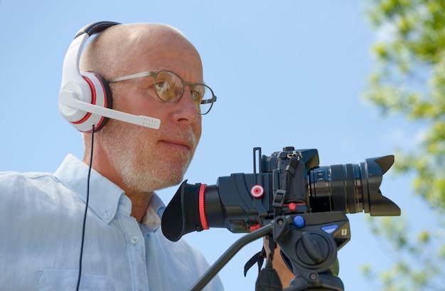 Homme avec un casque, à l'aide d'un appareil photo reflex numérique
