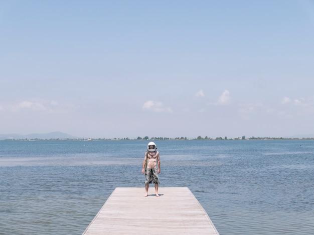 Homme avec casque d'astronaute sur la plage