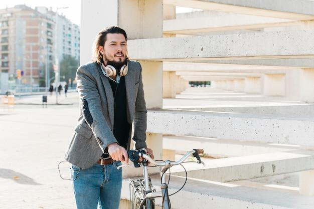 Un homme avec un casque autour du cou se tenant près du vélo