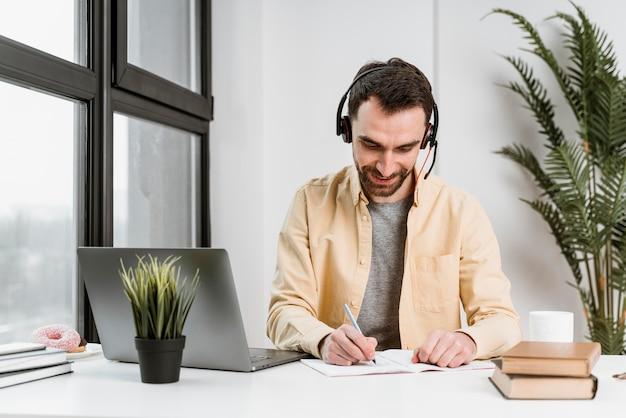 Homme avec casque ayant un appel vidéo sur ordinateur portable