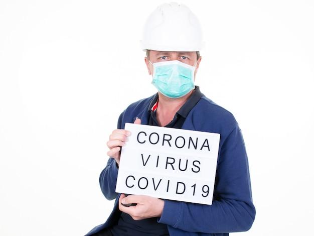 Homme avec un casque blanc et un masque de protection tenant une pancarte