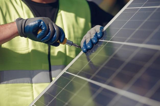 Homme avec un casque blanc près d'un panneau solaire