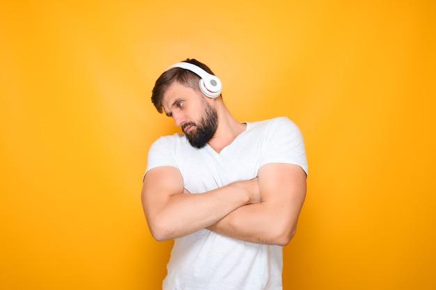 Un homme avec un casque a croisé les bras devant sa poitrine et écoute de la musique au casque.