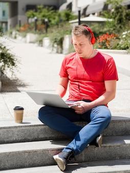 Homme avec un casque à l'extérieur avec café et ordinateur portable