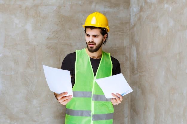 Homme en casque jaune et équipement vérifiant les fiches du projet