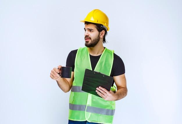 Homme avec un casque jaune tenant un dossier de projet et une tasse de café.