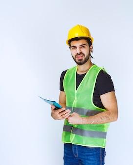 Homme avec un casque jaune tenant et vérifiant le dossier de projet bleu.
