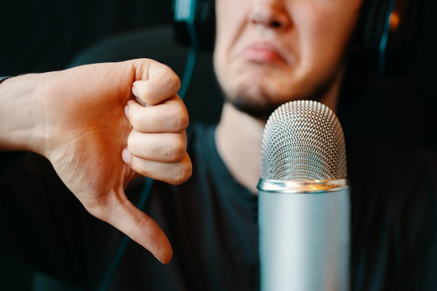 Homme avec casque et microphone dans le studio de podcast. je n'aime pas le geste. microphone vintage