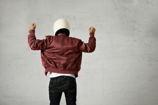 Homme en casque de moto blanc et veste de pilote bordeaux tiré de l'arrière avec les deux poings en l'air avec un geste shaka sur fond de mur blanc.