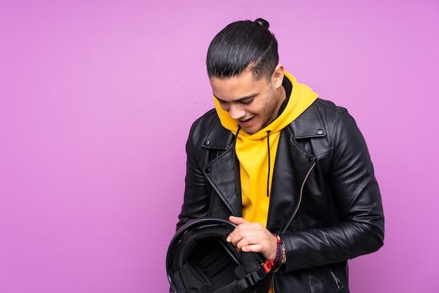 Homme avec un casque de moto isolé sur mur violet