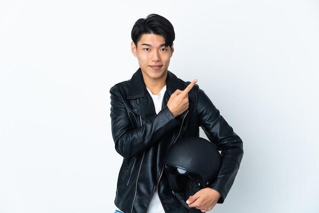 Homme avec un casque de moto isolé pointant vers le côté pour présenter un produit
