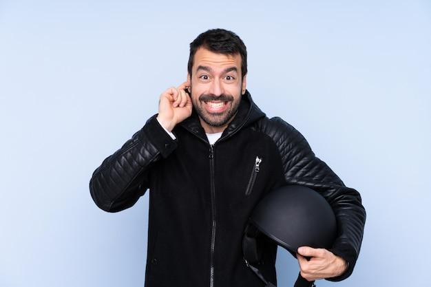 Homme avec un casque de moto sur un mur isolé frustré et couvrant les oreilles