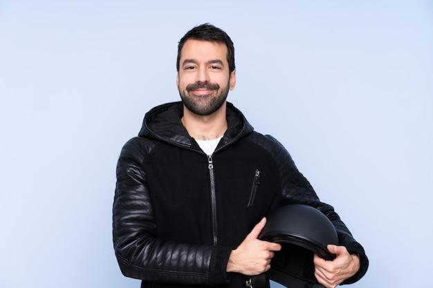 Homme avec un casque de moto sur un mur isolé en gardant les bras croisés en position frontale