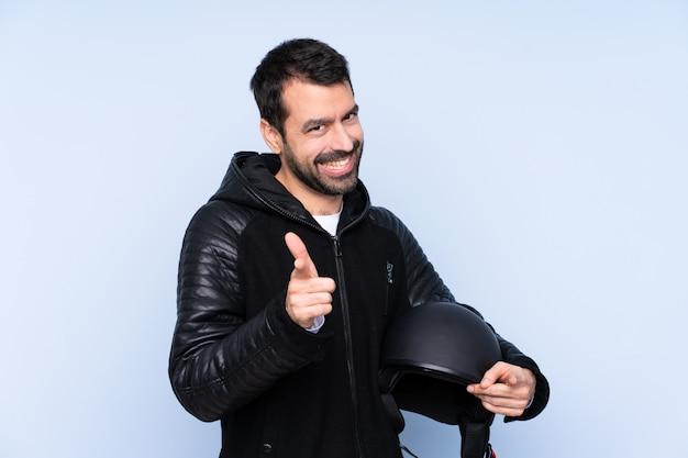 Homme avec un casque de moto sur un mur isolé pointant vers l'avant et souriant