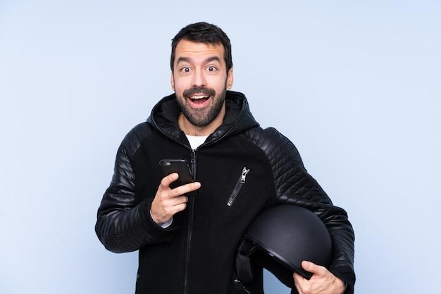 Homme avec un casque de moto sur un mur isolé surpris et envoyant un message