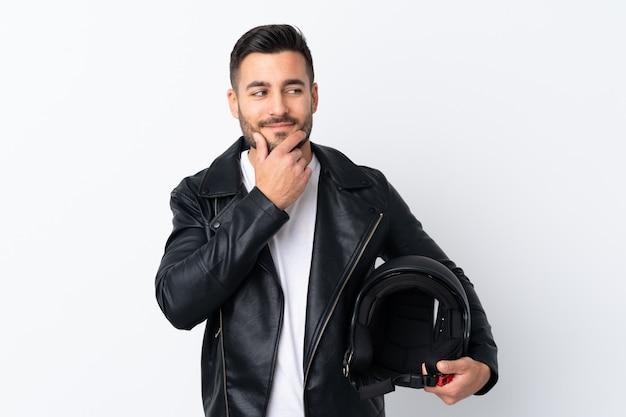 Homme avec un casque de moto pense à une idée