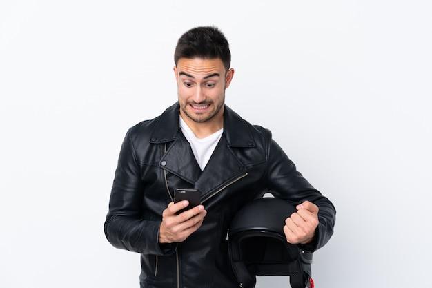 Homme avec un casque de moto surpris et envoyant un message