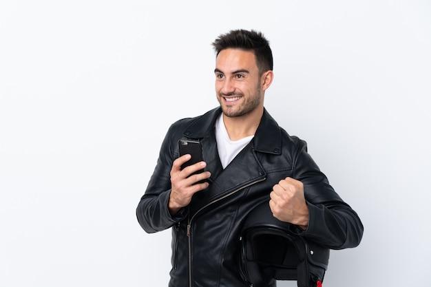 Homme avec un casque de moto avec téléphone en position de victoire