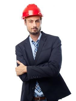 L'homme avec un casque rouge avec les bras croisés