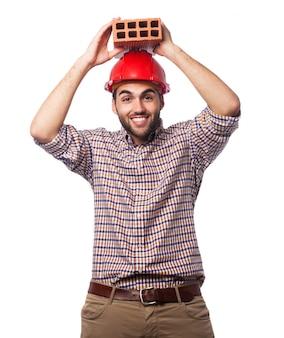 L'homme avec un casque rouge et une brique sur la tête