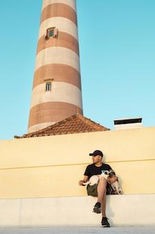 Homme en casquette et lunettes de soleil avec ses chiens au coucher du soleil à côté du phare d'aveiro au portugal